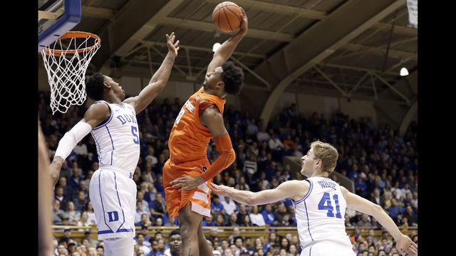 d4356cee2595 Duke s RJ Barrett (5) and Jack White (41) defend while Syracuse s Elijah  Hughes (33) drives to the basket during the first half of an NCAA college  ...