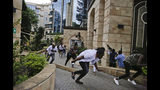 "Civilians flee as security forces aim their weapons at the buildings of a hotel complex in Nairobi, Kenya, Tuesday, Jan. 15, 2019. Extremists launched a deadly attack on a luxury hotel in Kenya's capital Tuesday, sending people fleeing in panic as explosions and heavy gunfire reverberated through the complex. A police officer said he saw bodies, ""but there was no time to count the dead."" (AP Photo/Khalil Senosi)"