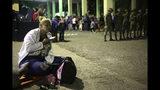 Una migrante hondureña escucha un celular meintras espera para entrar a Guatemala, en el paso fronterizo de Agua Caliente, Guatemala, el 15 de enero de 2019. (AP Foto/Moisés Castillo)