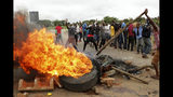 """FILE - In this Tuesday, Jan. 15, 2019 file photo, protestors gather near a burning tire during a demonstration over the hike in fuel prices in Harare, Zimbabwe. 2019 is already a busy year for internet shutdowns in Africa, with governments ordering cutoffs as soon as a crisis appears. Zimbabwe ordered a """"total internet shutdown"""" in recent days during protests over a dramatic fuel price increase and a resulting deadly crackdown. (AP Photo/Tsvangirayi Mukwazhi, File)"""