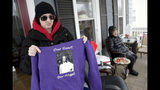 In a photo taken Friday, Jan. 18, 2019, Barbara Fuller, left, holds a sweatshirt honoring her late sister, Sarah Fuller, as their mother Deborah Fuller, right, looks on from their porch in West Berlin, N.J. The trial of the Insys Therapeutics Inc. founder John Kapoor, who accused of scheming to bribe doctors into prescribing a powerful painkiller, is putting a spotlight on the nation's deadly opioid crisis. (AP Photo/Julio Cortez)