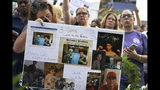 Jeanmarie McCauley, left, of Rockland, Mass., rests her head on a sign she made of her three children who died within three years to drug addiction, as family and friends who lost loved ones to OxyContin and opioid overdoses stage a protest outside the headquarters of Purdue Pharma in Stamford, Conn., on Friday, Aug. 17, 2018. (AP Photo/Jessica Hill)