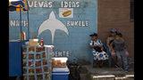 Vecinos se sientan junto a un mural que promueve la candidatura de Nayib Bukele, de la conservadora Gran Alianza para la Unidad Nacional (GANA), a las afueras de San Salvador, El Salvador, el viernes 1 de febrero de 2019. (AP Foto/Moises Castillo)