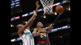 Atlanta Hawks guard Kent Bazemore (24) scores as Charlotte Hornets center Bismack Biyombo (8) defends during the first half of an NBA basketball Saturday, Feb. 9, 2019, in Atlanta. (AP Photo/John Bazemore)
