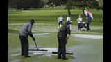 Si Woo Kim, second from right, of South Korea, stands with a rules officials and watches greenskeepers clear standing water from the second green of the Pebble Beach Golf Links during the final round of the AT&T Pebble Beach Pro-Am golf tournament Sunday, Feb. 10, 2019, in Pebble Beach, Calif. Play was suspended after a hail storm. (AP Photo/Eric Risberg)