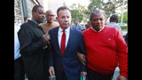 """FILE- In this Jan. 11, 2019, file photo, suspended Broward County Sheriff Scott Israel, center, leaves a news conference surrounded by supporters in Fort Lauderdale, Fla., after new Florida Gov. Ron DeSantis suspended him, over his handling of last February's massacre at Marjory Stoneman Douglas High School. Before the shooting, Israel had changed his department's policy to say deputies """"may"""" confront shooters from """"shall,"""" which critics say gave eight deputies who arrived during the shooting but stayed outside an excuse for not confronting the gunman. (AP Photo/Wilfredo Lee, File)"""