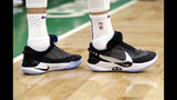 In this Feb. 7, 2019, photo, Los Angeles Lakers forward Kyle Kuzma stands on the court during an NBA basketball game against the Boston Celtics in Boston. He is wearing Nike's latest performance basketball shoes, which from concept to reality, took about three years to put together. Or 30 years, depending on how you count. The Nike Adapt BB _ a self-lacing smart shoe that can be controlled by a smartphone _ gets released to the public on Sunday, Feb. 17, 2019, a date that just happens to coincide with the NBA All-Star Game in Charlotte. It has a motor embedded within the shoe, and a hefty $350 price tag. (AP Photo/Elise Amendola)