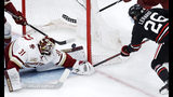 Boston College goaltender Joseph Woll (31) looks back as a shot by Northeastern forward Biagio Lerario (26) rolls over his pad, only to be knocked away by the stick of BC forward David Cotton during the first period of the NCAA hockey Beanpot tournament championship game in Boston, Monday, Feb. 11, 2019. (AP Photo/Charles Krupa)