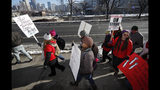 Teachers carry placards as they march along Speer Boulevard from West High School Monday, Feb. 11, 2019, in Denver. Denver teachers went on strike Monday after failing to reach a deal with administrators on pay in the latest example of educator discontent, following a wave of walkouts over the last year. (AP Photo/David Zalubowski)