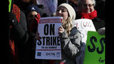 Rebecca Hendricks, a teacher at Emily Griffith High School, waves a sign during a strike rally on the west steps of the State Capitol Monday, Feb. 11, 2019, in Denver. The strike is the first for teachers in Denver since 1994 and centers on base pay. (AP Photo/David Zalubowski)