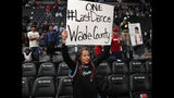 A Miami Heat fan holds up a sign for Heat guard Dwyane Wade in the first half of an NBA basketball game against the Denver Nuggets Monday, Feb. 11, 2019, in Denver. (AP Photo/David Zalubowski)