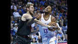 Oklahoma City Thunder forward Paul George (13) is fouled by Portland Trail Blazers forward Jake Layman, left, as he drives to the basket in the first half of an NBA basketball game in Oklahoma City, Monday, Feb. 11, 2019. (AP Photo/Sue Ogrocki)