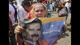 A supporter of Venezuela's President Nicolas Maduro holds a poster of him during a rally in Urena, Venezuela, Monday, Feb. 11, 2019. Nearly three weeks after the Trump administration backed an all-out effort to overthrow Maduro, the leader's hold on power appears shaken, but he's far from losing grip. The world watches now whether Maduro's government will let humanitarian aid from the United States cross its borders. (AP Photo/Fernando Llano)