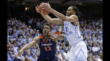 North Carolina's Garrison Brooks (15) and Virginia's De'Andre Hunter (12) reach for a rebound during the first half of an NCAA college basketball game in Chapel Hill, N.C., Monday, Feb. 11, 2019. (AP Photo/Gerry Broome)