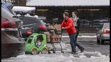 Jesse and Sarah Fees have their children along on a trip in North Tacoma, Wash., to restock their kitchen, Sunday, Feb. 10, 2019. Pacific Northwest residents who are more accustomed to rain than snow were digging out from a winter storm and bracing for more on Sunday. (Peter Haley/The News Tribune via AP)