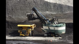FILE - In this April 4, 2013, file photo, a mechanized shovel loads a haul truck with coal at the Spring Creek coal mine near Decker, Mont. A judge says U.S. officials should reconsider the climate change effects of expanding the mine. (AP Photo/Matthew Brown, File)