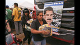 People carry bags with food provided by the Nicolas Maduro's government near the international bridge of Tienditas on the outskirts of Urena, Venezuela, Monday, Feb. 11, 2019. Nearly three weeks after the Trump administration backed an all-out effort to force out President Nicolas Maduro, the embattled socialist leader is holding strong and defying predictions of an imminent demise. (AP Photo/Fernando Llano)