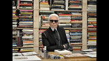 FILE - In this Feb. 14, 2014 file photo, fashion icon Karl Lagerfeld poses for photographers in front of his books prior to the start of an exhibition at the museum Folkwang in Essen, Germany. Chanel's iconic couturier, Karl Lagerfeld, whose accomplished designs as well as trademark white ponytail, high starched collars and dark enigmatic glasses dominated high fashion for the last 50 years, has died. He was around 85 years old. (AP Photo/Martin Meissner, File)
