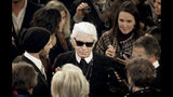 FILE - In this Tuesday, Dec. 10, 2013 file photo, Karl Lagerfeld, center wearing glasses, is greeted after the Chanel Metiers d'Art fashion show, in Dallas. Chanel's iconic couturier, Karl Lagerfeld, whose accomplished designs as well as trademark white ponytail, high starched collars and dark enigmatic glasses dominated high fashion for the last 50 years, has died. He was around 85 years old. (AP Photo/Tony Gutierrez, File)