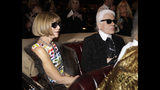 FILE - In this Tuesday, Dec. 10, 2013 file photo, Anna Wintour, left, the english editor-in-chief of American Vogue and designer Karl Lagerfeld sit in a vintage car as they wait to view a movie short of Coco Chanel's return to fashion after closing her house during WWII before the start of Chanel's Metiers d'Art fashion show, in Dallas. Chanel's iconic couturier, Karl Lagerfeld, whose accomplished designs as well as trademark white ponytail, high starched collars and dark enigmatic glasses dominated high fashion for the last 50 years, has died. He was around 85 years old. (AP Photo/Tony Gutierrez, File)