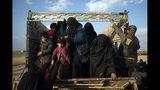 Mujeres y niños bajan de un camión, parte de una caravana que los evacúa del último territorio en poder de los milicianos del Estado Islámico en Baghouz, este de Siria, viernes 22 de febrero de 2019. (AP Foto/Felipe Dana)