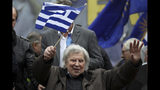 "FILE - In this Sunday, Feb. 4, 2018 file photo, famous Greek composer Mikis Theodorakis holds a Greek flag waves after his speech at a rally in Athens. ""Zorba the Greek"" composer Mikis Theodorakis has undergone surgery in Athens to have a pacemaker installed, according to a hospital statement Friday March 8, 2019, saying the 94-year old Theodorakis, is recuperating from the operation Friday.(AP Photo/Petros Giannakouris, File)"