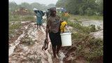 People trudge through a muddied path to safer ground in Chimanimani, about 600 kilometers southeast of Harare, Zimbabwe, Monday, March 18, 2019. (AP Photo/Tsvangirayi Mukwazhi)