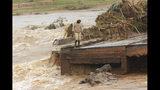 A man stands on the edge of a collapsed bridge in Chimanimani, about 600 kilometers southeast of Harare, Zimbabwe, Monday, March 18, 2019. (AP Photo/Tsvangirayi Mukwazhi)