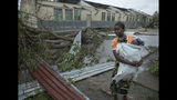 A woman makes her way to a school building being used as an emergency shelter for some 300 local people who are unable to return to their homes following cyclone force winds and heavy rain in the coastal city of Beira, Mozambique, Sunday March 17, 2019. More than 1,000 people are feared dead in Mozambique four days after a cyclone slammed into the southern African country destroying vulnerable residential areas. (Josh Estey/CARE via AP)