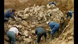 FILE - In this Sept. 18, 1996 file photo, International War Crimes Tribunal investigators clear away soil and debris from dozens of Srebrenica victims buried in a mass grave near the village of Pilica, north east of Tuzla, Boisnia-Herzegovina. Nearly a quarter of a century since Bosnia's devastating war ended, former Bosnian Serb leader Radovan Karadzic is set to hear the final judgment on whether he can be held criminally responsible for unleashing a wave of murder and destruction during Europe's bloodiest carnage since World War II. United Nations appeals judges on Wednesday March 20, 2019, will decide whether to uphold or overturn Karadzic's 2016 convictions for genocide, crimes against humanity and war crimes and his 40-year sentence. (AP Photo/Staton R. Winter, File)