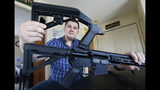 In this March 15, 2019 photo, Ryan Liskey displays a bump stock on top of his AR-15 at his home in Harrisonburg, Va. The ban on bump stocks is just a few days away and owners of the devices like Liskey are trying to figure out what to do. (AP Photo/Steve Helber)