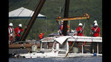 FILE- In this July 23, 2018, file photo the duck boat that sank on July 19 in Table Rock Lake in Branson, Mo., is raised. The company that owns the boat that sank last summer, killing 17 people, announced Thursday, March 21, 2019, that it won't operate the vessels this year because of the ongoing investigation and will instead open a replacement attraction in the tourist town of Branson. (Nathan Papes/The Springfield News-Leader via AP, File)