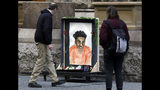 Passers-by looks at a memorial display with a drawing of Antwon Rose II in front of the Allegheny County courthouse on the second day of the trial for Michael Rosfeld, a former police officer in East Pittsburgh, Pa., Wednesday, March 20, 2019. Rosfeld is charged with homicide in the fatal shooting of Antwon Rose II as he fled during a traffic stop on June 19, 2018. (AP Photo/Gene J. Puskar)