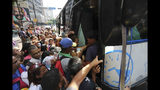 People jockey to enter a bus during a power outage that suspended the subway service in Caracas, Venezuela, Monday, March 25, 2019. (AP Photo/Fernando Llano)