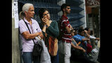 A woman tries to make a cell phone call during a power outage where commuters wait for buses while the subway service is suspended in Caracas, Venezuela, Monday, March 25, 2019. (AP Photo/Fernando Llano)
