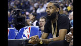 FILE - In this March 29, 2018, file photo, rapper Nipsey Hussle watches an NBA basketball game between the Golden State Warriors and the Milwaukee Bucks in Oakland, Calif. Grammy-nominated and widely respected West Coast rapper Nipsey Hussle has been shot and killed outside his Los Angeles clothing store, Los Angeles Mayor Eric Garcetti said Sunday, March 31, 2019. He was 33. (AP Photo/Marcio Jose Sanchez, File)