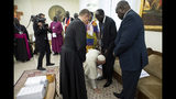 Pope Francis kneels to kiss the feet of South Sudan's President Salva Kiir Mayardit, at the Vatican, Thursday, April 11, 2019. Pope Francis has closed a two-day retreat with South Sudan authorities at the Vatican with an unprecedented act of respect, kneeling down and kissing the feet of the African leaders. (Vatican Media via AP)