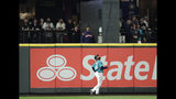 Seattle Mariners left fielder Domingo Santana tracks a grand slam hit by Houston Astros' Yuli Gurriel as it sails into the Mariners' bullpen during the eighth inning of a baseball game Friday, April 12, 2019, in Seattle. (AP Photo/Ted S. Warren)