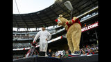 """Atlanta Braves mascot """"Blooper,"""" right, tees off from the top of a dugout as his Masters-clad caddie stands by before a baseball game against the New York Mets, Sunday, April 14, 2019, in Atlanta. (AP Photo/John Amis)"""