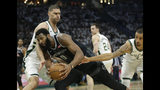 Detroit Pistons' Andre Drummond (0) is fouled as he drives between Milwaukee Bucks' Brook Lopez and George Hill during the first half of Game 1 of an NBA basketball first-round playoff series Sunday, April 14, 2019, in Milwaukee. (AP Photo/Aaron Gash)
