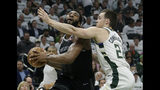 Detroit Pistons' Andre Drummond, left, drives to the basket against Milwaukee Bucks' Pat Connaughton during the first half of Game 1 of an NBA basketball first-round playoff series Sunday, April 14, 2019, in Milwaukee. (AP Photo/Aaron Gash)