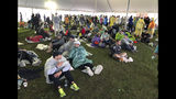 Runners wait under a tent while it rains before the start of the 123rd Boston Marathon on Monday, April 15, 2019, in Hopkinton, Mass. (AP Photo/Jennifer McDermott)