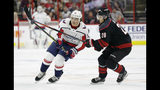 Carolina Hurricanes' Sebastian Aho (20), of Finland, and Washington Capitals' T.J. Oshie (77) chase the puck during the first period of Game 3 of an NHL hockey first-round playoff series in Raleigh, N.C., Monday, April 15, 2019. (AP Photo/Gerry Broome)