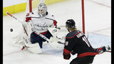 Carolina Hurricanes' Dougie Hamilton (19) shoots on goal while Washington Capitals goalie Braden Holtby (70) defends during the second period of Game 3 of an NHL hockey first-round playoff series in Raleigh, N.C., Monday, April 15, 2019. (AP Photo/Gerry Broome)