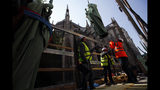 Workers secure a religious statue perched atop Paris' Notre Dame Cathedral as it descends to earth for the first time in over a century as part of a restoration, in Paris Thursday, April 11, 2019. The 16 greenish-gray copper statues, which represent the twelve apostles and four evangelists, are lowered by a 100 meter (105 yard) crane onto a truck to be taken for restoration in southwestern France. (AP Photo/Francois Mori)
