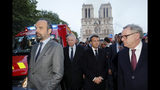 French Prime Minister Edouard Philippe, left, and French President Emmanuel Macron walk by Notre Dame cathedral in Paris, Monday, April 15, 2019. A catastrophic fire engulfed the upper reaches of Paris' soaring Notre Dame Cathedral as it was undergoing renovations Monday, threatening one of the greatest architectural treasures of the Western world as tourists and Parisians looked on aghast from the streets below.(Philippe Wojazer/Pool via AP)