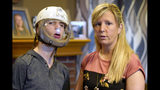 In this April 11, 2019 photo, Shelley Gillen is photographed in her Bellevue, Neb., home with her 17-year-old son, Will, who wears a helmet to protect him from damage during debilitating seizures. Gillen advocates the legalization of medical marijuana that could help her son's seizures. Nebraska's conservative lawmakers are poised to once again reject measures calling for allowing limited and highly regulated use of medical marijuana, but their decision this year could have the unintended consequence of ushering in one of the most unrestricted medical marijuana laws in the country. (AP Photo/Nati Harnik)