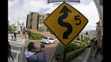 A man takes pictures as cars wind their way down Lombard Street in San Francisco, Monday, April 15, 2019. Thousands of tourists may soon have to pay as much as $10 to drive down the world-famous curvy street if a proposal to establish a toll and reservation system becomes law. In the summer months, an estimated 6,000 people a day visit the 600-foot-long street, creating lines of cars that stretch for blocks. (AP Photo/Eric Risberg)