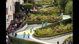 FILE - In this Aug. 19, 2009 file photo, children run down Lombard Street in San Francisco, transformed for the day into a gigantic Candy Land board game to commemorate the game's 60th anniversary. Tourists may soon have to pay a fee to drive down San Francisco's world-famous crooked street. California officials plan to announce a proposal Monday, April 15, 2019 that would grant San Francisco permission to establish a toll and reservation system. (AP Photo/Marcio Jose Sanchez, File)