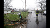 A Shelby firefighter walks down Plymouth Springmill Road just south of the intersection of Ohio Route 96, past severe storm damage to homes in Shelby, Ohio, Sunday, April 14, 2019. (Tom E. Puskar/The Times Gazette via AP)